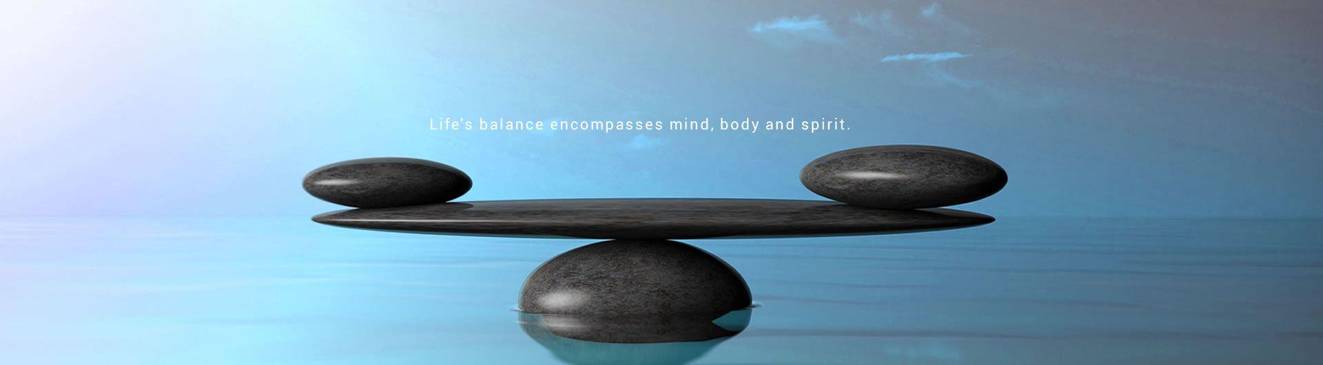 balancing stones on blue background